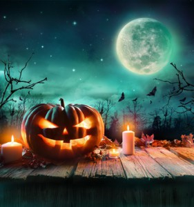 Halloween Pumpkin On Wooden Plank With Candles In A Spooky Night
